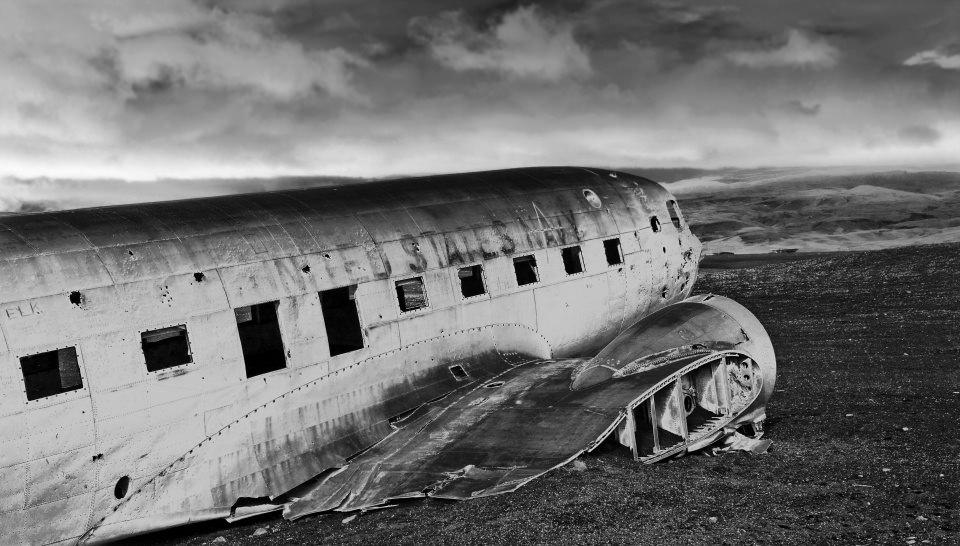 Flugzeugwrack in einer Landschaft in schwarzweiß.