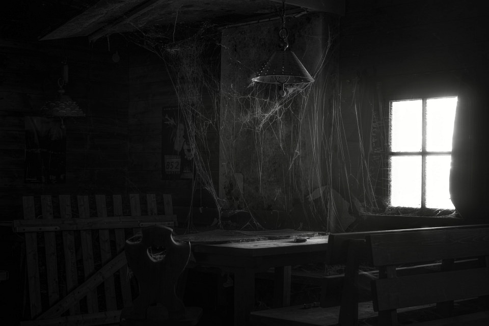 Dunkles Zimmer voller Spinnenweben.