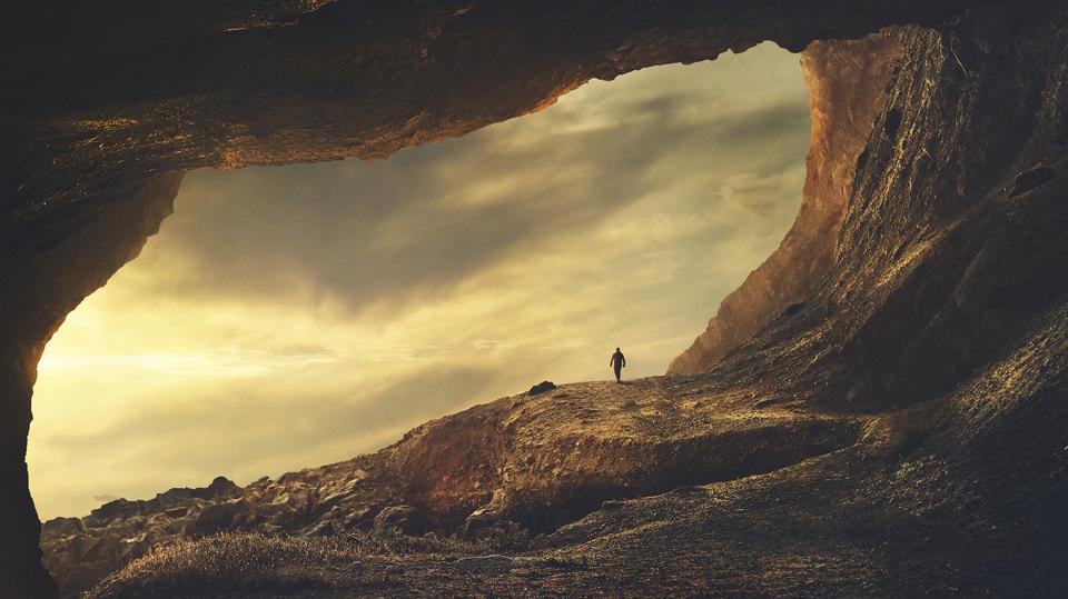 Eine Höhle, ein Mensch und goldenes Licht.