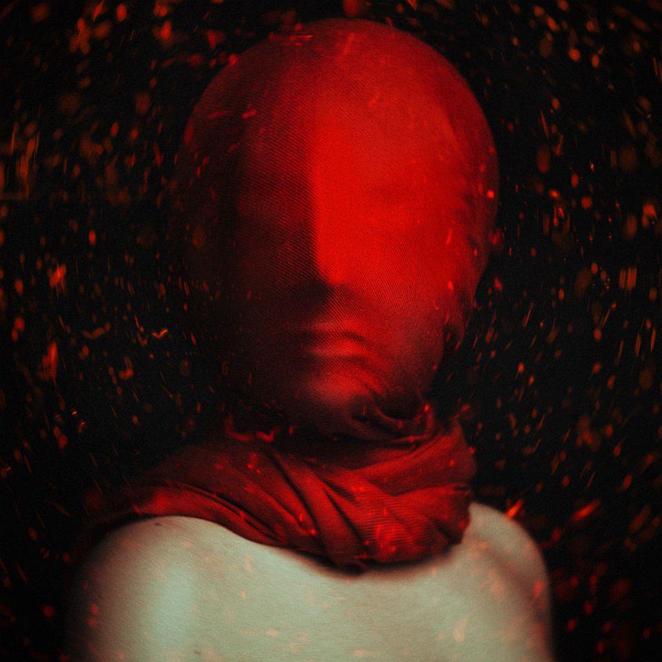 Mensch mit einem roten Tuch eng um den Kopf und von roten, flirrenden Lichtern umgeben.