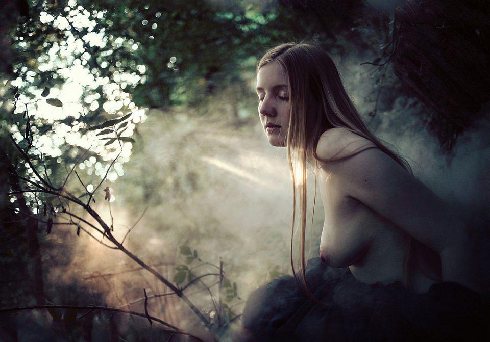 Frauenakt in der Natur mit Nebel und sanften Lichtstrahlen.