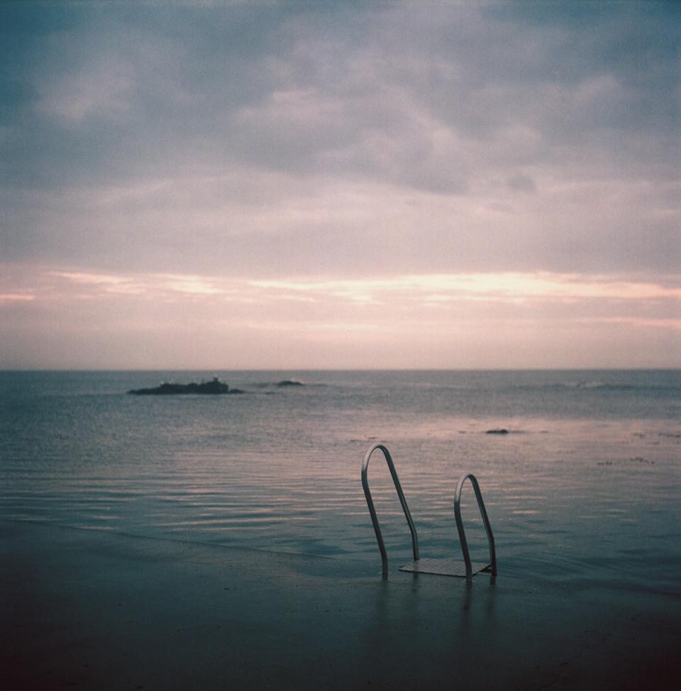 Poolleiter ganz vom Wasser umgeben, mit Horizont und Wolken in rosa.