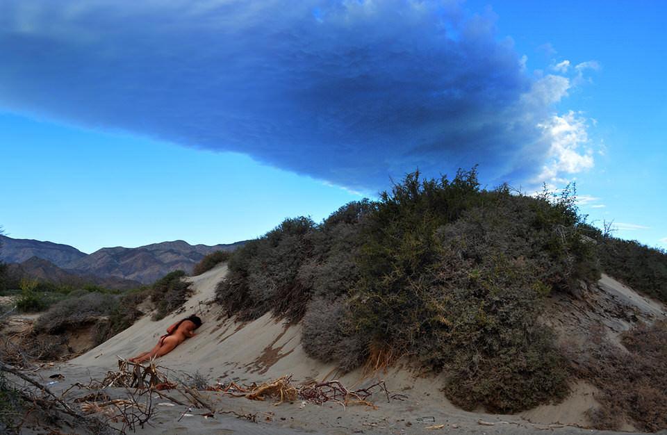 Eine Frau liegt mit dem Gesicht nach unten auf einer Sanddüne.