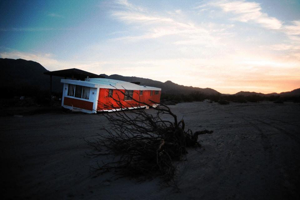 Ein rotes Haus und ein toter Baum.