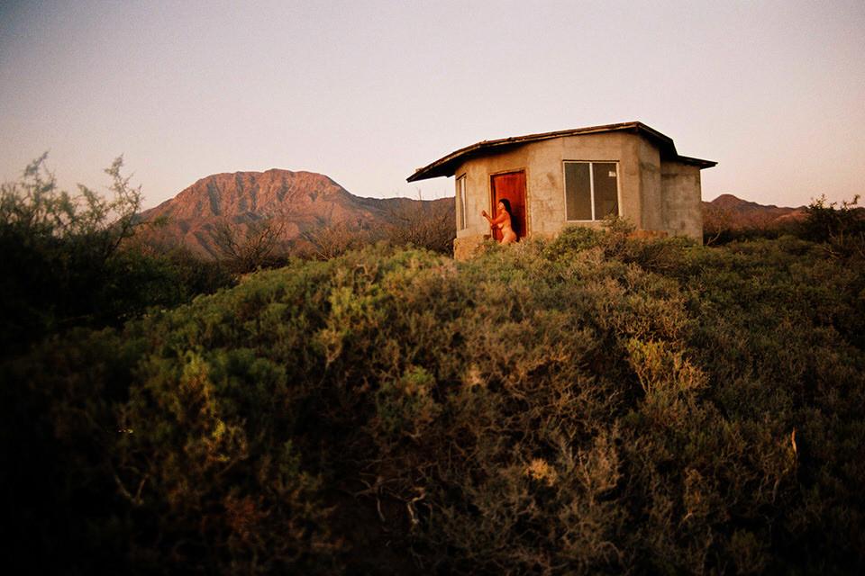 Eine Frau steht nackt vor einem kleinen Haus.