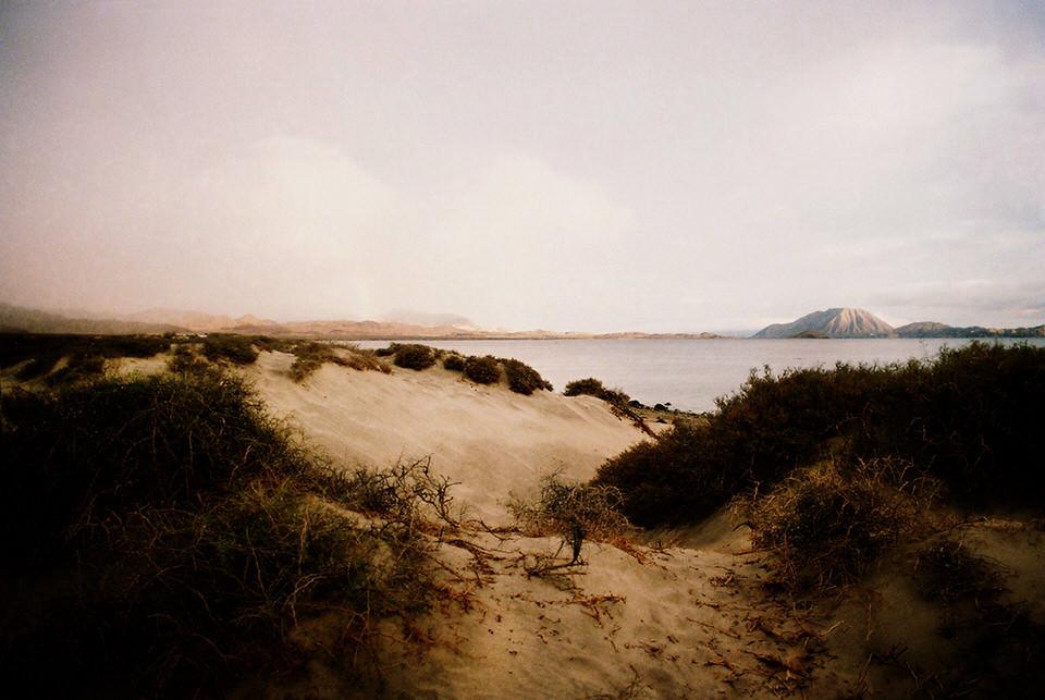 Eine Sanddüne. Im Hintergrund das Meer und ein Berg.
