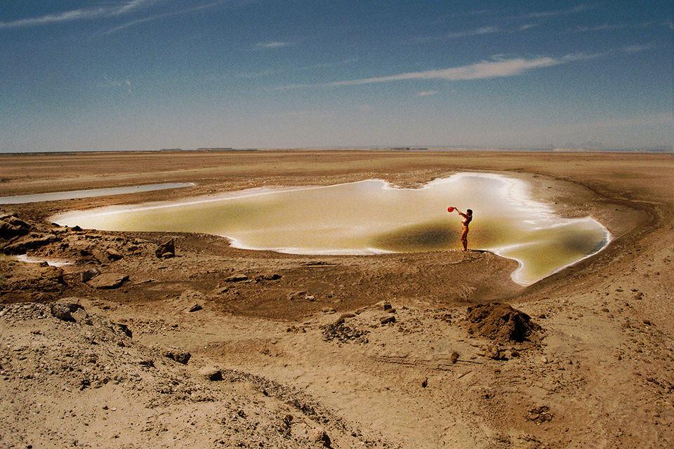 Eine Frau mit einem roten Ballon vor einem Tümpel in der Wüste.