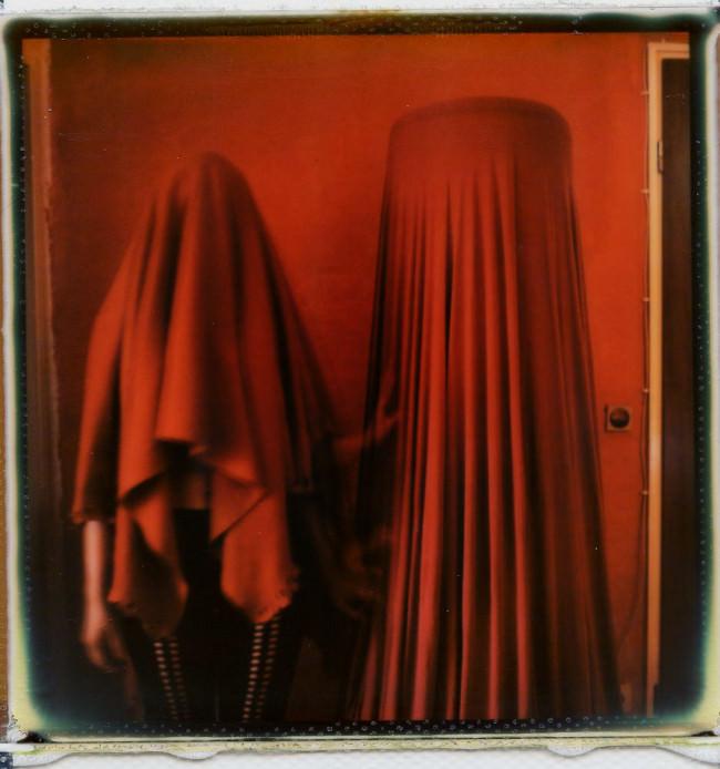 Eine Frau und eine Lampe unter einem Tuch verborgen.