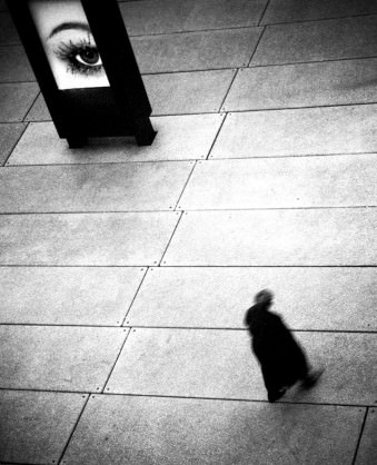 Ein Mann läuft einen Platz entlang. Ein Auge auf einem Plakat beobachtet ihn.