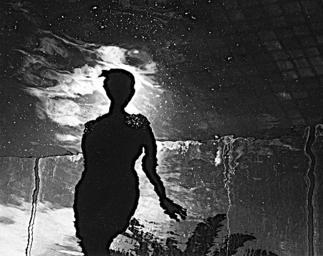 Eine Spiegelung einer Frau in einer Pfütze.
