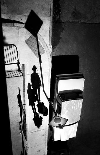 Twei Menschen gehen an einem parkenden Auto vorbei und werden dabei von oben fotografiert.