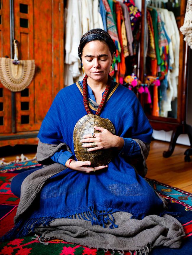 Eine Frau mit einem Schildkrötenpanzer sitzt am Boden.