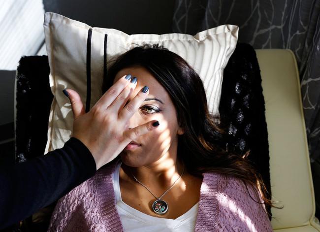 Eine Frau liegt auf einbem Bett. Eine Hand wird vor ihr Gesicht gehalten.