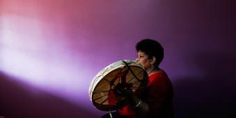 Eine Frau mit Trommel vor einer lilanen Wand.