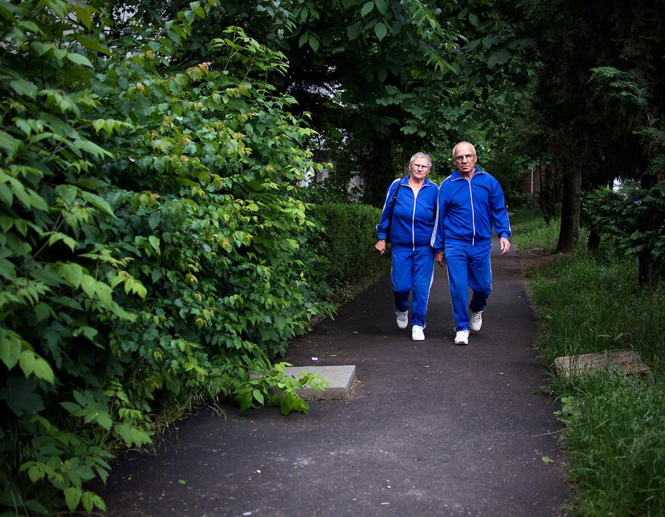 Ein Paar in blauen Jogginganzügen neben einer Hecke