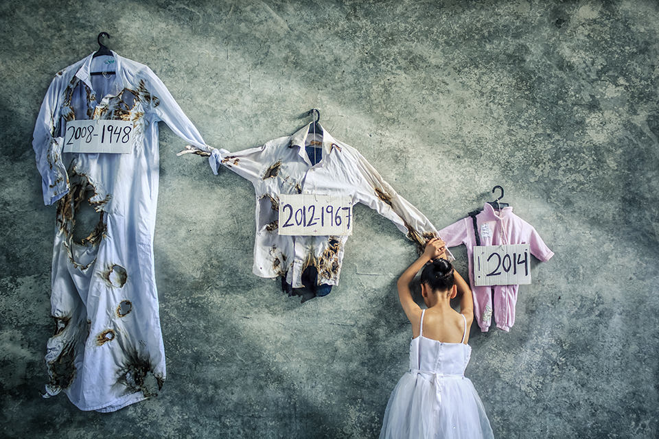 Mädchen in weißem Kleid vor kaputter Kleidung
