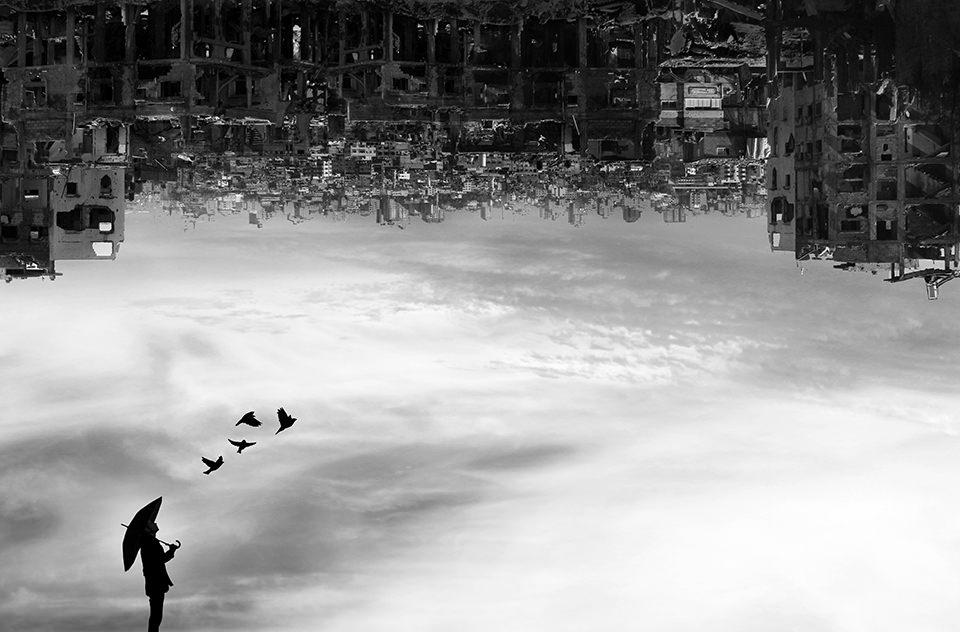 Person steht unter einem Himmel aus Ruinen