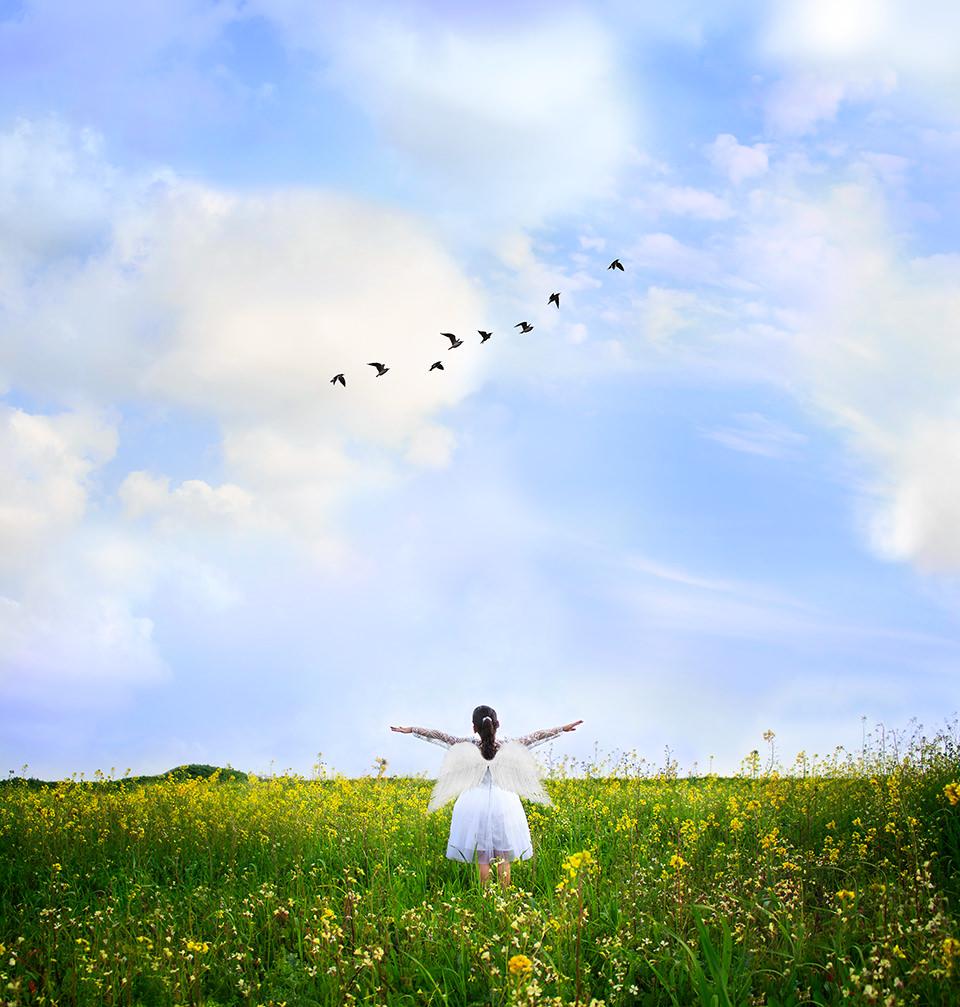 Kind mit Engelsflügeln rennt durch ein Feld