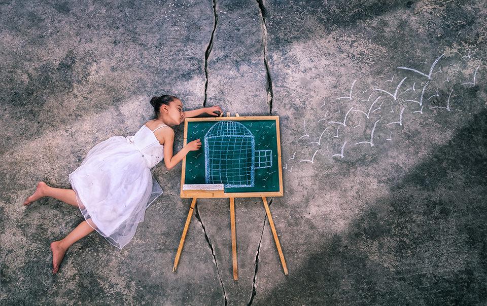Mädchen vor einer Tafel mit einer Zeichnung eines Vogelkäfigs