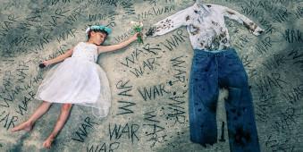 """Kind neben zerfetzter Kleidung, auf dem Boden steht """"War"""""""