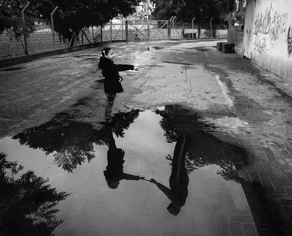 Kind vor einer Spiegelung in einer Pfütze