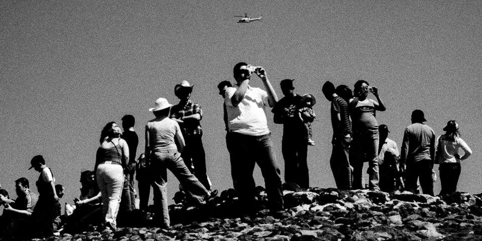 Menschen stehen auf einem Berg und schauen in die Ferne.
