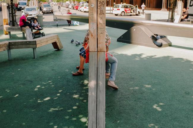 Beine zweier Personen, die von einem Balken verdeckt sind.