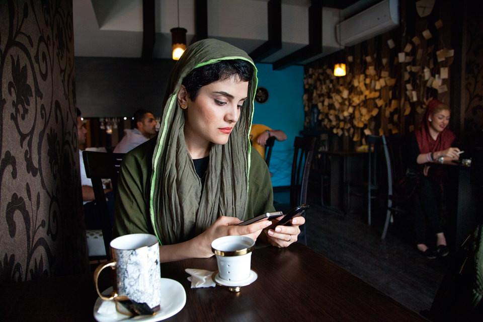 Eine Frau mit Handy und Kaffeetasse an einer Bar.