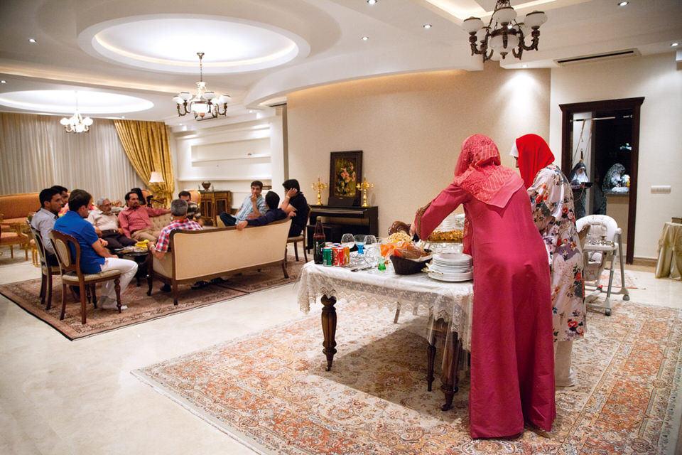 Zwei Frauen stehen an einem Tisch voller Essen. Im Hintergrund sitzt eine Gruppe Männer an einem Tisch.
