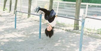 Ein Kind hängt kopfüber über einer Stange