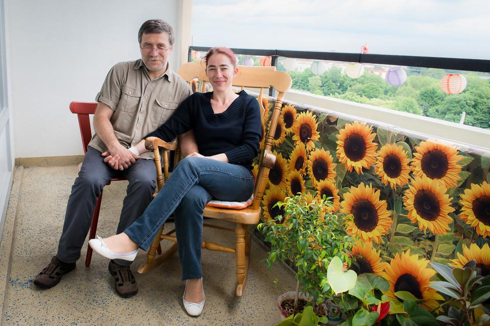 Ein Paar und Sonnenblumen schauen in die Kamera.