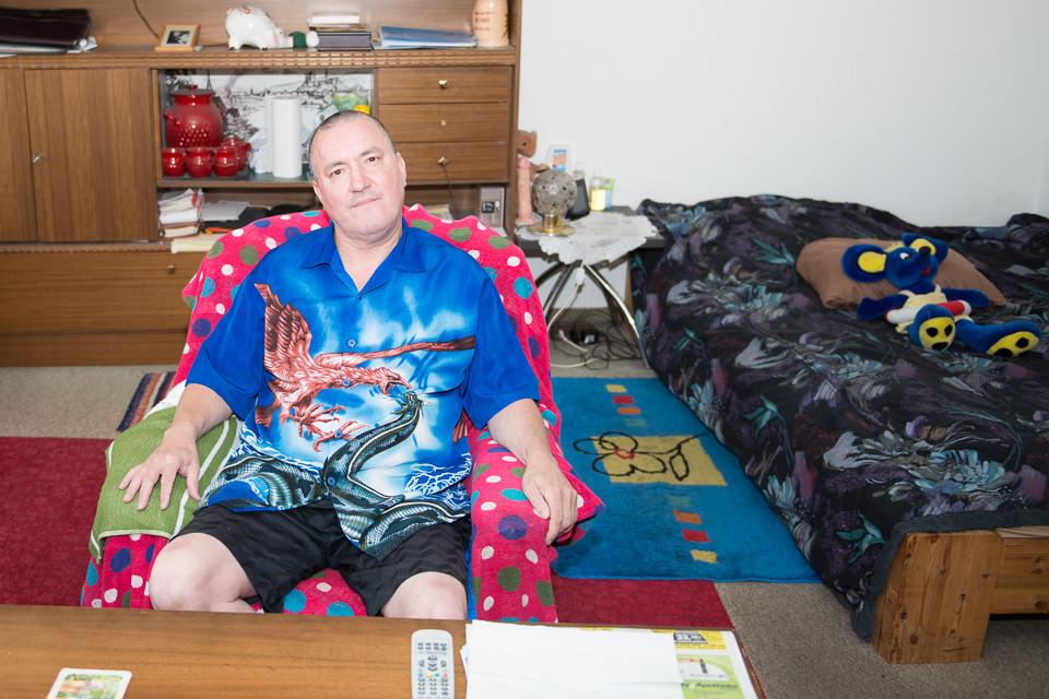 Ein Mann in einem bunten Hemd und einer Schrankwand.