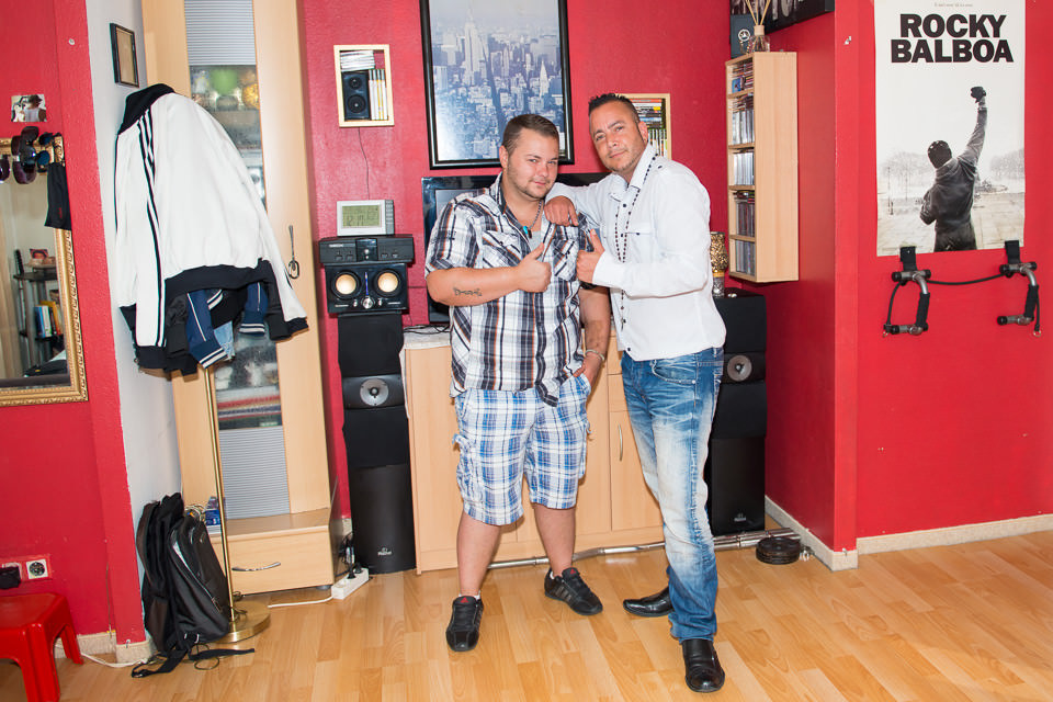 Zwei Männer stehen im Wohnzimmer.