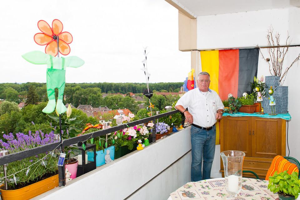Ein Mann steht auf seinem Balkon.
