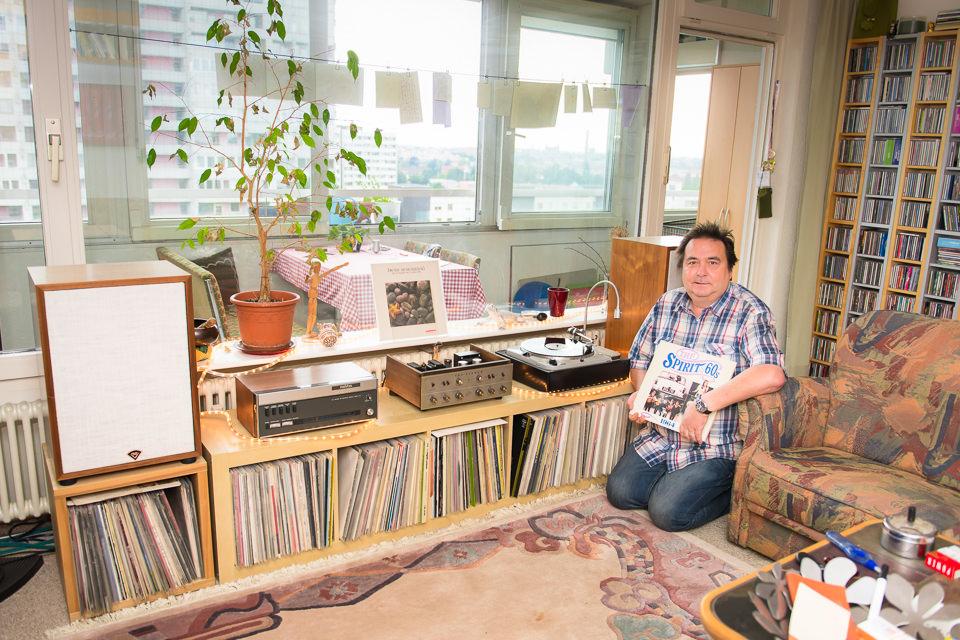Ein Mann sitzt vor seinem Schallplattenregal.