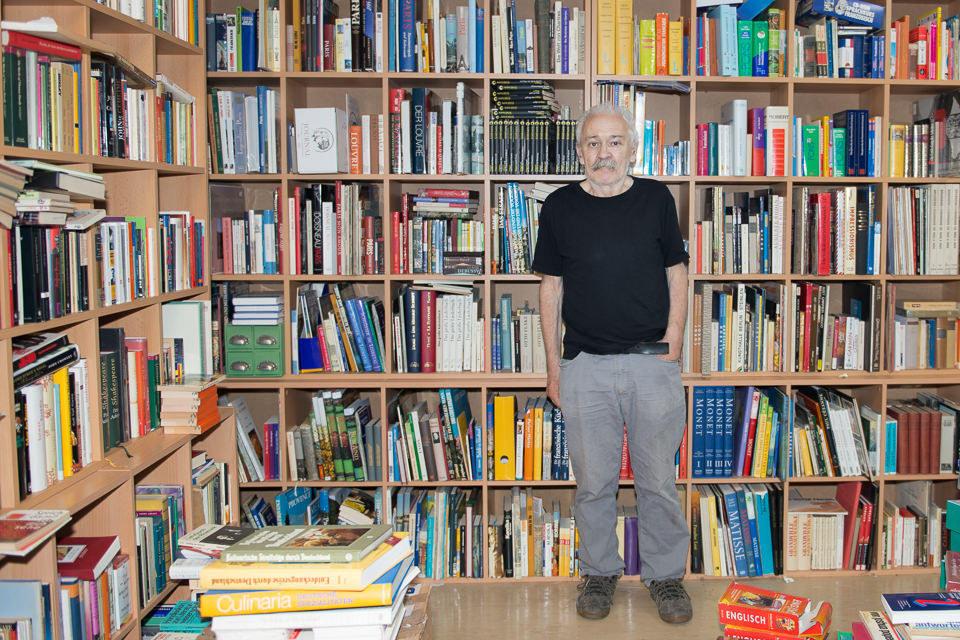 Ein Mann steht vor seinem Bücherregal.