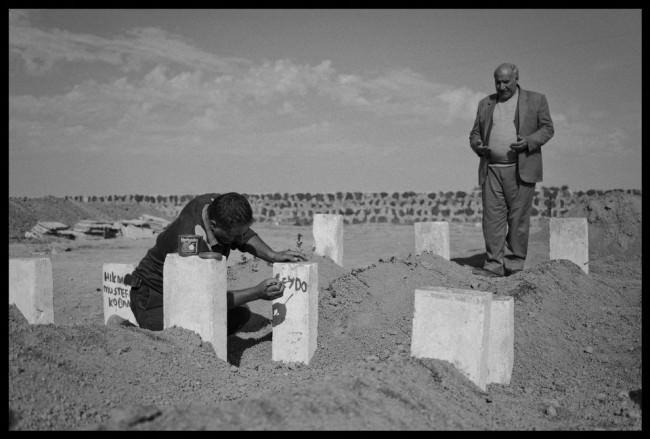 Friedhof Suruc: Ein Kurde betet vor den Gräber der YPJ-Kämpfer, während ihre Namem aufgeschrieben werden.