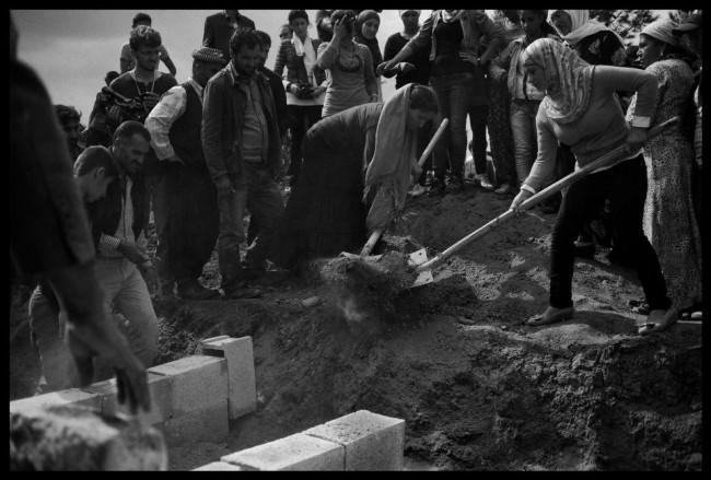 Kurdische Männer und Frauen begraben einen Kämpfer, der im Kampf gegen den IS gestorben war.