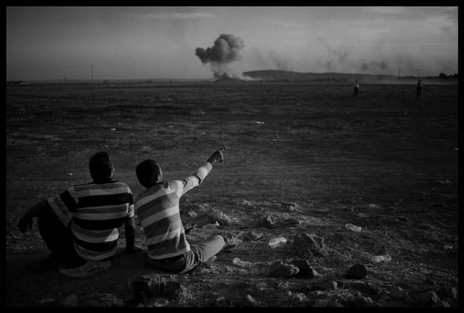 Kurdische Männer schauen von der türkischen Grenze in Suruc auf Kobane, das von alliierten Kräften bombardiert wird.