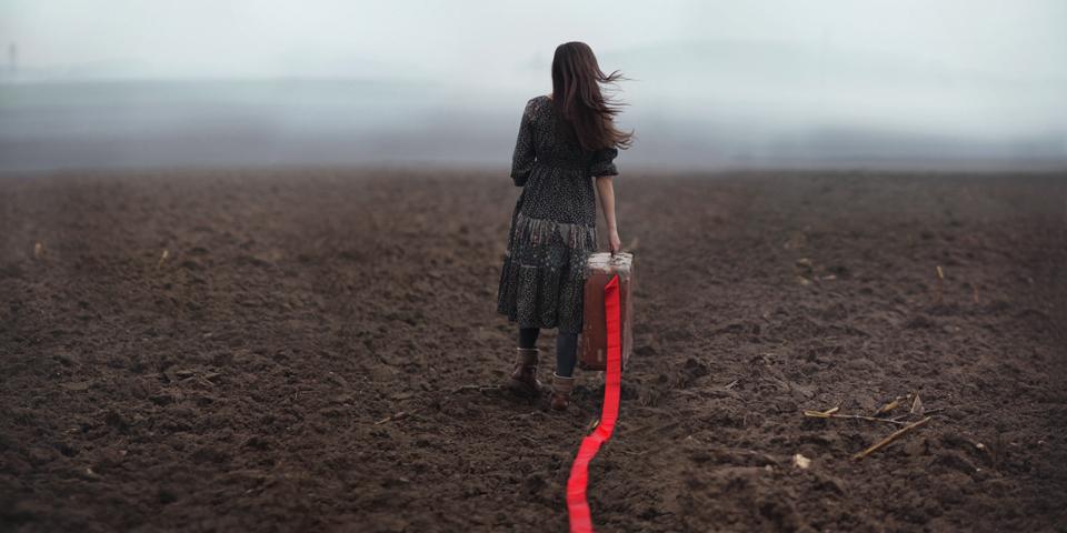 Ein Mädchen läuft über einen nebeligen Acker und zieht ein rotes Band hinter sich her.