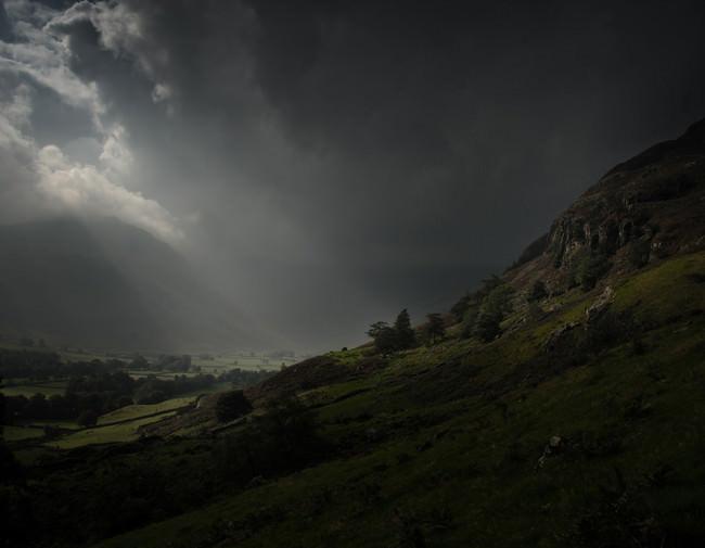 Ein Lichtstrahl durchdringt Wolken und trifft auf einen Berg.