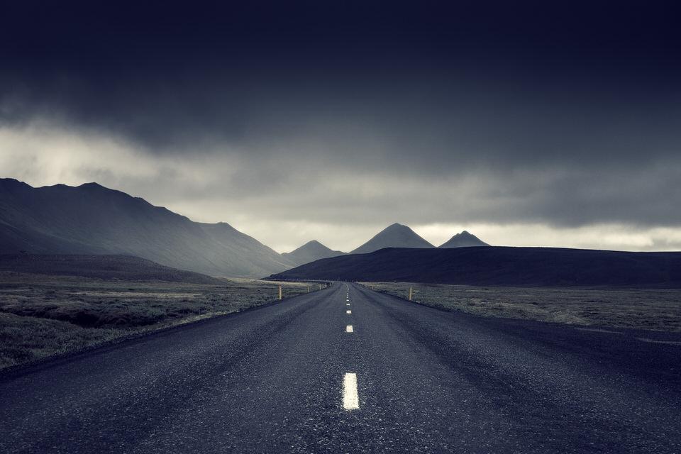 Eine endlose Straße führt durch eine weite, bewölkte Landschaft.