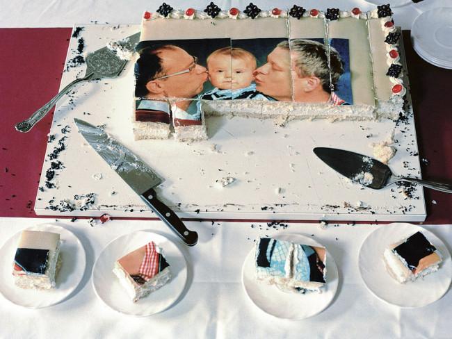 Blick auf eine Torte, auf der zwei Männer ein einem Kind einen Kuss geben.