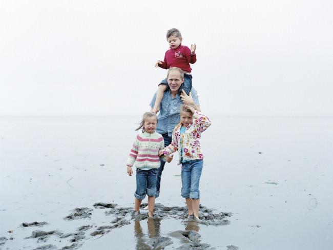 Ein Vater mit seinen Kindern im Meer.