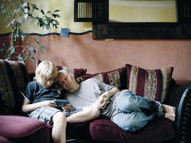 Ein Vater schläft auf der Couch an der Schulter eines Kindes, während das ein Videospiel spielt.