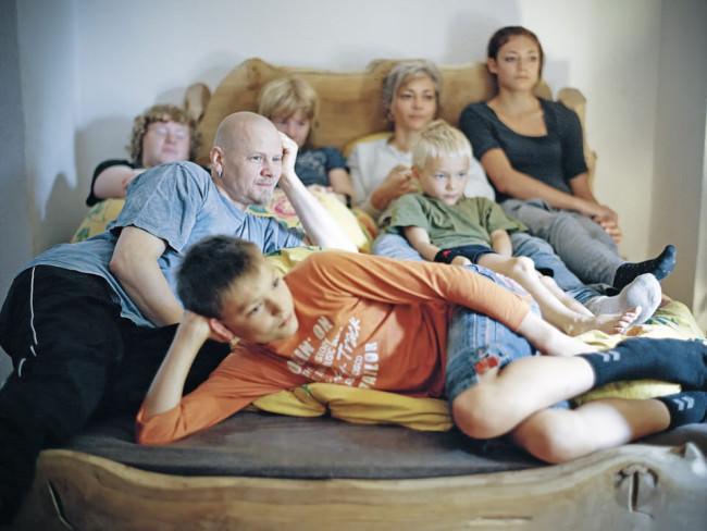 Eine Familie liegt auf dem Bett und schaut Fernsehen.