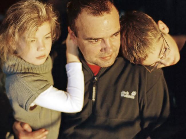 Ein Vater mit zwei Kindern auf dem Arm.