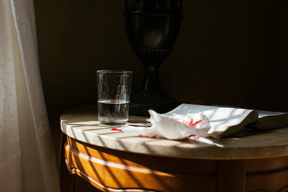 Ein Nachtisch mit einem Glas Wasser, einem Buch und einem Taschentuch mit roten Flecken.