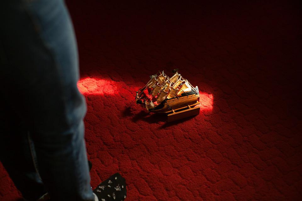 Ein Modellschiff liegt im Lichtschein auf einem roten Teppich.