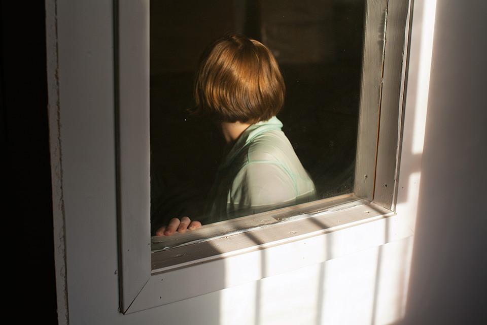 Eine Frau von hinten im Fenster einer Tür.
